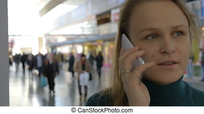 Woman talking on the phone at the station - Young woman...