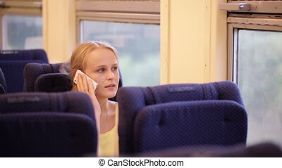 Woman talking on the phone being on the train.
