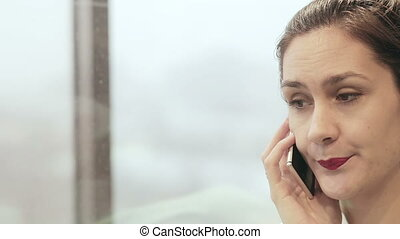 Woman talking on the phone in a moving elevator