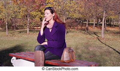 Woman talking on the phone in the Park on a bench