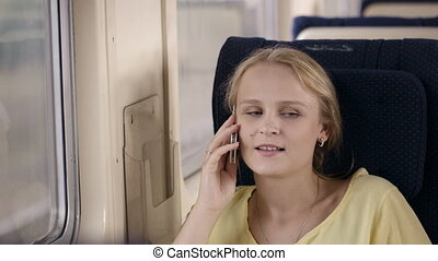 Woman talking on the phone in the train.