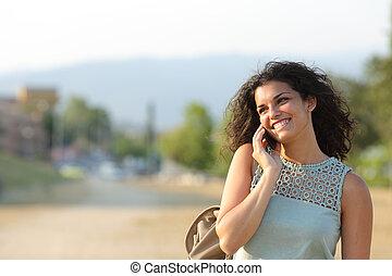 Woman talking on the phone walking in a park - Woman talking...