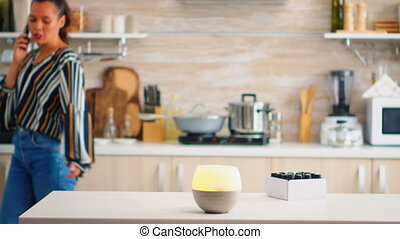 Woman talking on the phone with essential oils aromatherapy next to her in the kitchen. Aroma health essence, welness aromatherapy home spa fragrance tranquil theraphy, therapeutic steam, mental health treatment