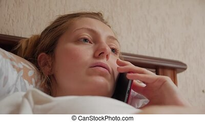 Woman talking on the phone lying in bed with braces closeup