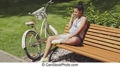 Woman talking phone on bench - Young woman talking...