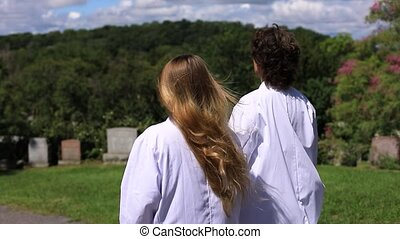 Two young woman in conversation pointing towards something while walking in graveyard after mourning for deceased person due to covid-19