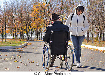 Woman talking to a disabled man in a wheelchair