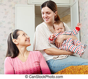 woman talking to adult daughter with granddaughter