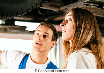 Woman talking to car mechanic in repair shop