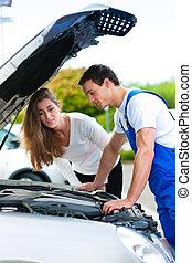 Woman talking to car mechanic in repair shop - Woman talking...