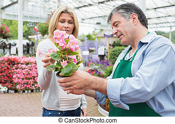 Woman talking to employee about plant in garden center