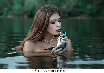Woman talking to fish. - The woman is in water and talks to ...