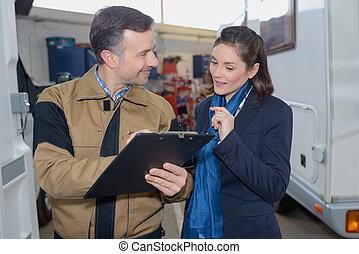 Woman talking to mechanic