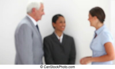 Woman talking to people before coming into focus against...