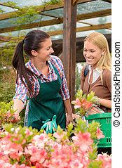Woman talking to worker in garden center