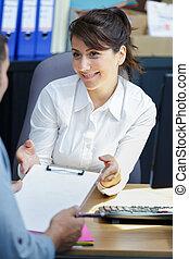 woman talking to worker in office