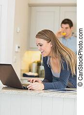 Woman talking via Webcam with man drinking orange juice