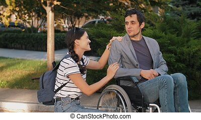 Woman talking with a man in a wheelchair