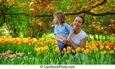 Woman talking with little girl in park among blossoming...