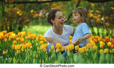 Woman talking with little girl in park among blossoming tulips