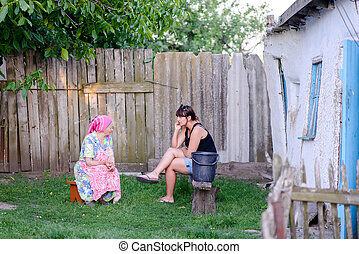 Woman Talking with Mother Outdoors in Yard