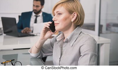 Woman Talks on Phone in Office