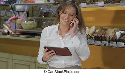 Woman talks on the phone at the pastry shop