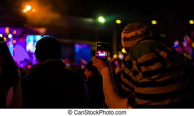 Woman Taping Concert In The Crowd With A Child On Shoulders Using Smartphone