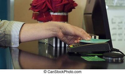Woman tapping credit card on payment terminal. Person using...