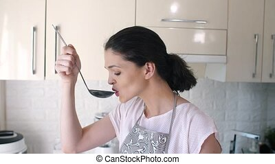 Woman tastes soup before serving - Beautiful young brunette...
