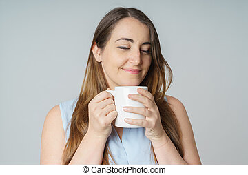 Woman tasting a cup of tea