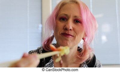 Happy modern woman, with pink hair, eating a salad of sashimi salmon, on white background. Slow motion close up on chopsticks.