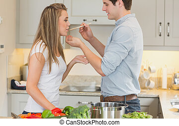 Woman tasting sauce from pot