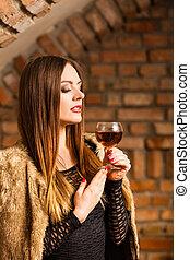 Woman tasting wine in rural cottage interior