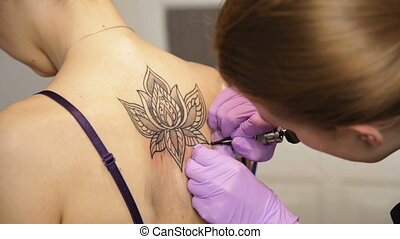 tattoo master is making tattoo flower - Woman tattoo master...