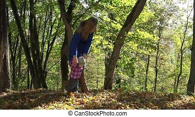 Woman teach baby child walking in autumn forest. 4K