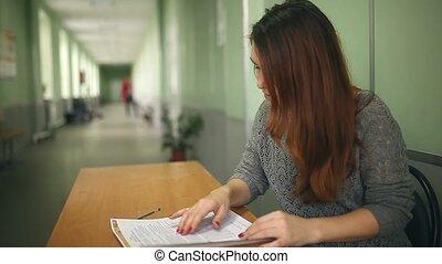 Woman teacher checks homework sitting at a desk in school hallway
