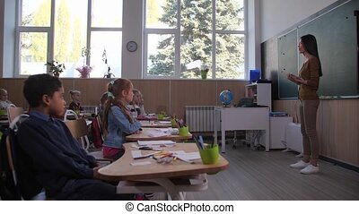 Woman teacher communicating with pupils in class