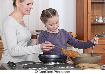 Woman teaching her daughter how to make crepes