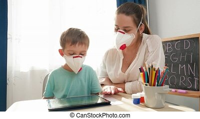 Woman teaching little boy using tablet computer wearing medical mask respirator. Distance education and remote school at home during lockdown and self isolation