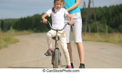 Woman teaching little girl to ride a bicycle