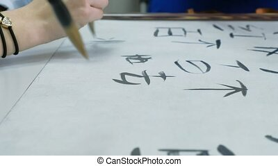 Woman teaching teen how to write Chinese characters at...