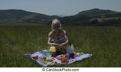 Woman Tears Apart Croissant - Woman on picnic tearing apart...