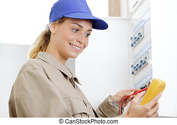 woman technician reading the voltage of a fuseboad meter