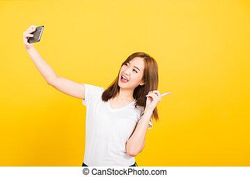 woman teen smiling standing wear t-shirt making selfie photo, video call on smartphone