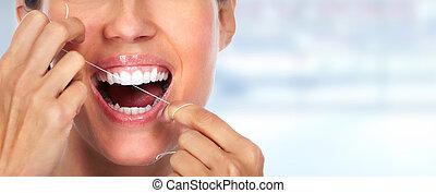Woman teeth with dental floss. Dentistry health care.