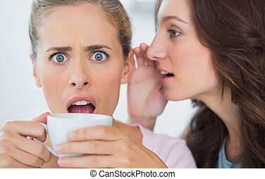 Woman telling secret to her friend and astonishing her