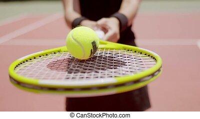 Woman tennis player balancing a ball on her racket