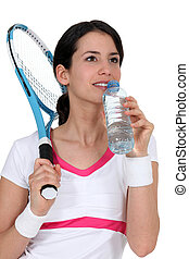 Woman tennis player drinking water