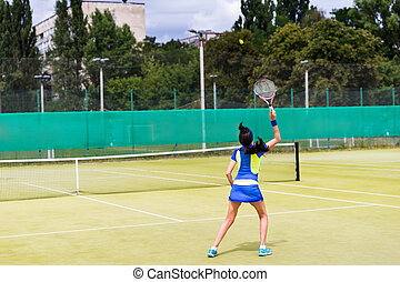 Woman tennis player in action on a court outdoor
